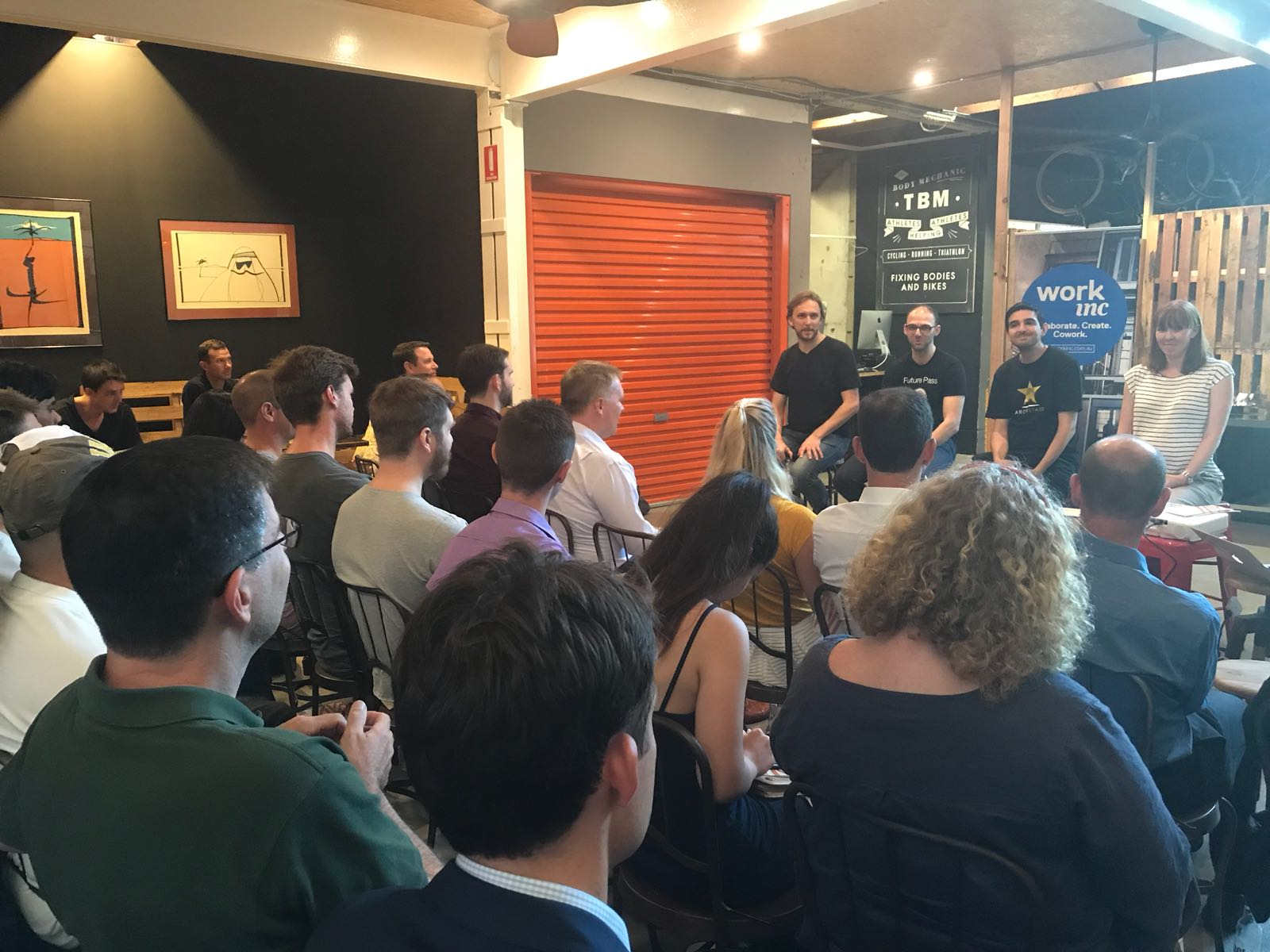 Photo of people in the room and Mark Baartse, Chris Iona, Robert Coorey & Rebekah Campbell speaking at NSIN's Accelerating your Startup Event